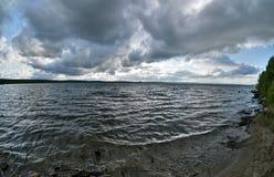 Ciel gris-foncé au-dessus du lac agité images stock