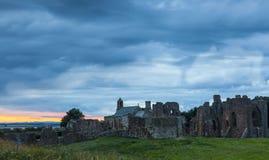 Ciel lourd au coucher du soleil au-dessus du prieuré de Lindisfarne, île sainte photographie stock