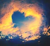 Ciel lumineux dans un coucher du soleil, forme de coeur Image libre de droits