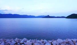 Ciel, montagnes, mur en pierre et lac paisible Image libre de droits