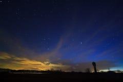 Ciel nocturne avec des nuages au-dessus du champ Image stock