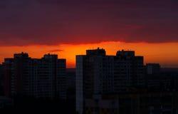 Ciel nocturne avec le coucher du soleil rouge dans la ville Photos stock