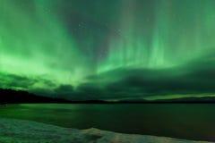 Ciel nocturne d'aurora borealis au-dessus de lac congelé Laberge Photo libre de droits