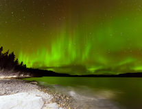 Ciel nocturne d'aurora borealis au-dessus de lac Laberge le Yukon Photographie stock libre de droits
