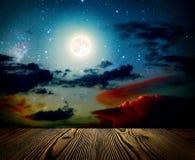 Ciel nocturne de milieux avec les étoiles, la lune et les nuages Étage en bois Image stock