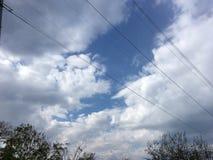 Ciel nuageux, arbres, fils de rue Images stock