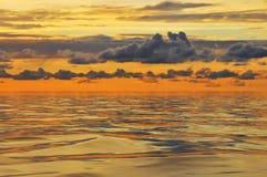 Ciel nuageux au coucher du soleil et aux réflexions dans l'eau photos stock