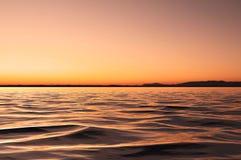 Ciel nuageux au coucher du soleil et aux réflexions dans l'eau images stock