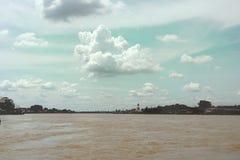 Ciel nuageux au-dessus de Muddy River avec la statue d'or de Bouddha photos libres de droits