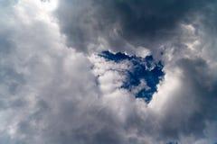 Ciel nuageux blanc avec un trou de ciel bleu en forme de triangle au centre image stock