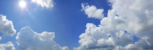 Ciel nuageux bleu avec le soleil Photographie stock libre de droits