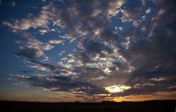 Ciel nuageux bleu de beau coucher du soleil Photos stock