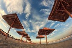 Ciel nuageux de coucher du soleil sur une belle plage de mer avec des parapluies de paille Séance photos grande-angulaire d'oeil  Image libre de droits