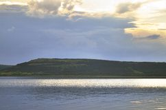 Ciel nuageux et grand lac près des montagnes Photographie stock libre de droits