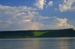 Ciel nuageux et lac dans les montagnes vertes Photos libres de droits