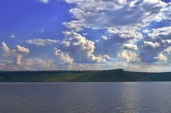 Ciel nuageux et rivière dans le paysage vert Image libre de droits