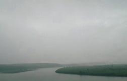 Ciel nuageux gris sur la rivière Photos stock