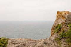 Ciel nuageux, mer et un morceau de roche photo stock