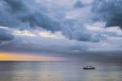 Ciel nuageux stupéfiant de coucher du soleil avec le bateau dans Bali photos libres de droits