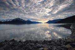 Ciel obscurci réfléchissant sur l'eau Image stock