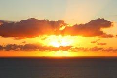 Ciel orange au-dessus de mer par coucher du soleil Image libre de droits
