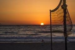 Ciel orange, mer bleue et filet de volleyball Images libres de droits