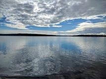 Ciel partiellement nuageux se reflétant dans l'océan Image stock
