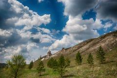 Ciel profond et bleu avec les nuages volumineux au-dessus du temple crayeux dans Kostomarovo images stock