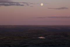 Ciel rose mou de coucher du soleil au-dessus de vallée de montagne avec la pleine lune Photos libres de droits