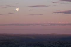 Ciel rose mou de coucher du soleil au-dessus de vallée de montagne avec la pleine lune Photos stock