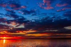 Ciel vibrant coloré dramatique de coucher du soleil avec des nuages reflétés dans l'eau images libres de droits
