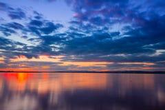Ciel vibrant coloré dramatique de coucher du soleil avec des nuages reflétés dans l'eau photographie stock