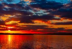 Ciel vibrant coloré dramatique de coucher du soleil avec des nuages reflétés dans l'eau photos stock