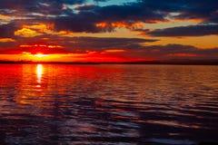 Ciel vibrant coloré dramatique de coucher du soleil avec des nuages reflétés dans l'eau photos libres de droits