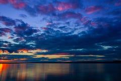 Ciel vibrant coloré dramatique de coucher du soleil avec des nuages reflétés dans l'eau images stock