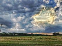 Cieli nuvolosi d'apertura sopra il terreno coltivabile di estate Immagini Stock