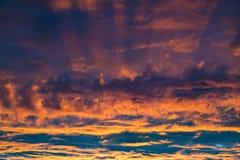 Cielo al tramonto Tramonto fantastico variopinto - nuvole arancio illuminate dai fasci del tramonto contro il cielo porpora scuro immagine stock