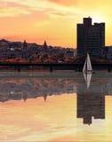 Cielo amarillo con reflexiones hermosas en el agua con un velero Imagen de archivo libre de regalías