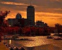 Cielo anaranjado y amarillo brillante para hacer juego las hojas de otoño con los edificios en el lago Fotografía de archivo libre de regalías