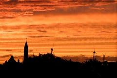Cielo arancio di sera con i mulini a vento sull'orizzonte Fotografie Stock Libere da Diritti
