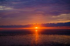 Cielo arancio di tramonto con i raggi del sole Immagini Stock
