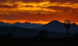 Cielo arancio profondo con un punto di vista contrapposto del paese di un mulino a vento fotografia stock