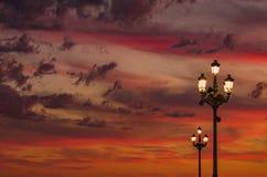 Cielo ardiente de la puesta del sol con el farol imagenes de archivo