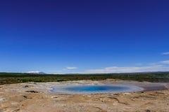 Cielo azul brillante sobre el valle de géiseres en Islandia fotos de archivo