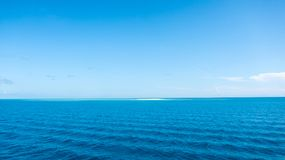 Cielo azul con la pequeña isla en el océano azul, un sueño imágenes de archivo libres de regalías