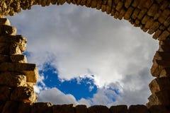 Cielo azul con las nubes enmarcadas por el arco antiguo de ladrillos, espacio de la copia Foto de archivo