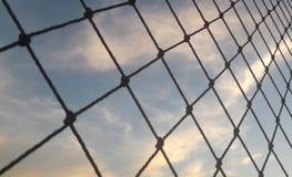 Cielo azul con las nubes a través de una red Imagen de archivo