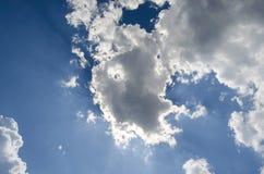 Cielo azul con las nubes y el sol blancos sobre ellos Imagenes de archivo