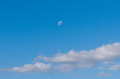 Cielo azul con las nubes y la luna. imagen de archivo