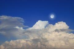 Cielo azul con las nubes y la luna Fotografía de archivo